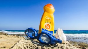 tub of sunscreen on beach